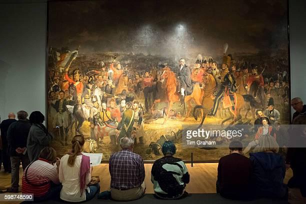 Visitors viewing Jan Willem Pieneman 'The Battle of Waterloo' oil on canvas painting at Rijksmuseum Amsterdam Holland
