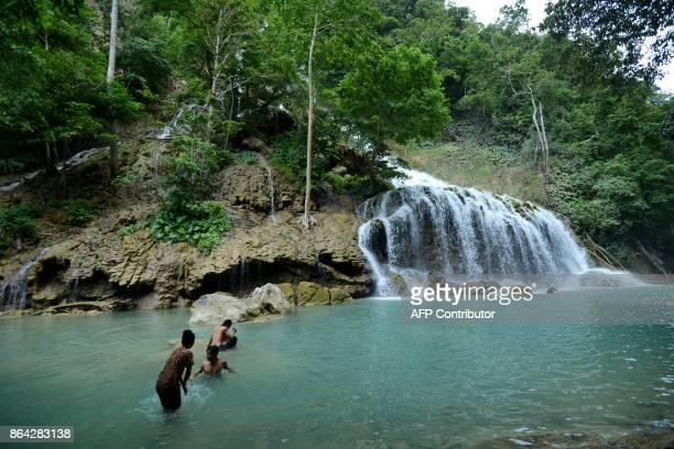 Visitors visit the Lapopu waterfall in West Sumba in East Nusa Tenggara Province on October 21 2017 / AFP PHOTO / Sonny TUMBELAKA