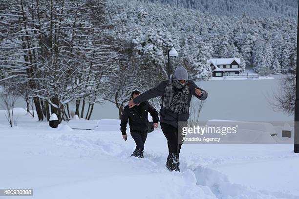 Visitors wade through the snow near the frozen lake and lake house at the Golcuk Natural Park in Bolu city of Turkey during the winter season on...