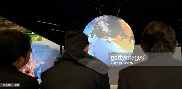 Visitors wait by a planisphere on the US stand at the COP 21 United Nations conference on climate change on December 4 2015 in Le Bourget At the...