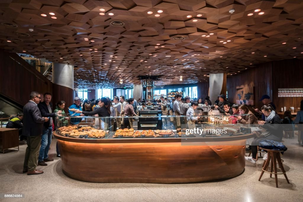 Visitors wait for their coffee at the Starbucks Reserve Roastery outlet in Shanghai on December 6, 2017. Starbucks opened its largest cafe in the world in Shanghai on December 6 as the US-based beverage giant bets big on the burgeoning coffee culture of a country traditionally known for tea-drinking. / AFP PHOTO / - / China OUT
