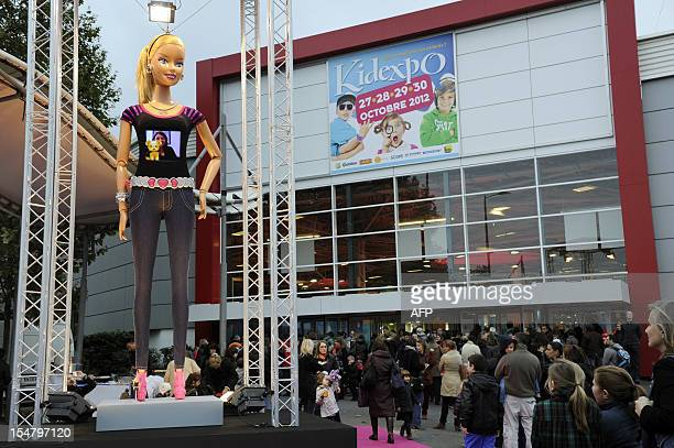 Visitors wait in front of a fivemeter high replica of a Barbie doll displayed at the entrance of the 'Kidexpo' show on October 26 at outside the...