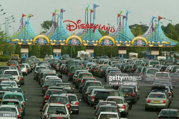 Visitors wait in line at the entrance in their cars at Disneyland Paris August 22 2002 in Marne la Vallee France After a rocky start ten years ago...