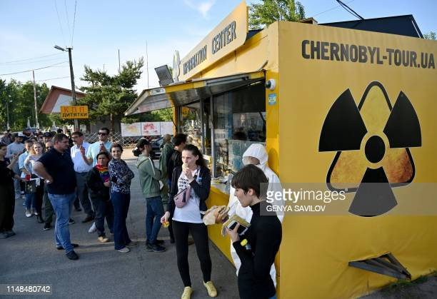 Visitors wait in line to buy snacks and souvenirs at a souvenir shop next to the Dytyatky checkpoint after a tour in the Chernobyl exclusion zone on...