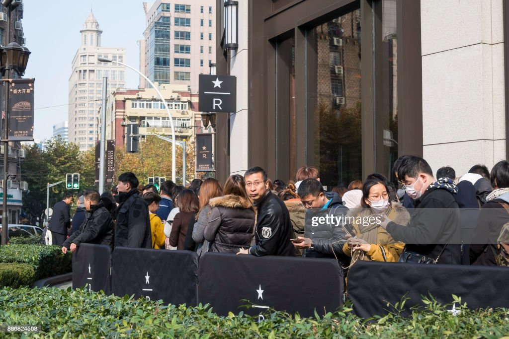 Visitors wait to enter the Starbucks Reserve Roastery outlet in Shanghai on December 6, 2017. Starbucks opened its largest cafe in the world in Shanghai on December 6 as the US-based beverage giant bets big on the burgeoning coffee culture of a country traditionally known for tea-drinking. / AFP PHOTO / - / China OUT