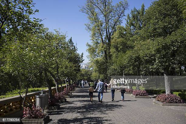 Visitors walk a path that leads to the Chapultepec Castle which houses Mexico's National Museum of History inside the first section of Chapultepec...
