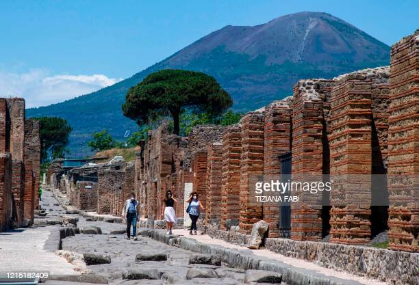 Visitors walk across the archeological site of Pompeii at the bottom of the Mount Vesuvius volcano on May 26 as the country eases its lockdown aimed...