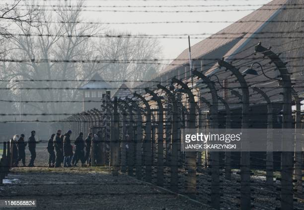 Visitors walk across the barbed wire fences of the Auschwitz German Nazi death camp ahead of German Chancellor Angela Merkel's landmark visit in...