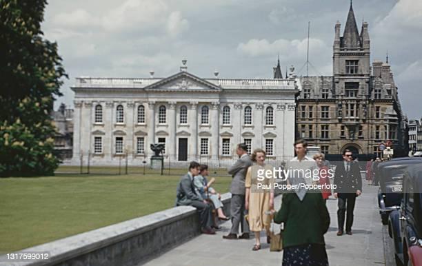 Visitors walk along King's Parade beside the lawn outside the University of Cambridge Senate House in Cambridge, England circa 1960. Behind Senate...