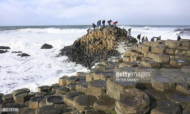 Visitors walk along the basalt rocks at the Giants Causeway in Northern Ireland on March 12 2008 Gale force winds are affecting the UK with many...