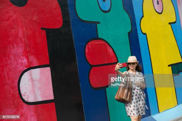 Visitors walk along the East Side Gallery a milelong section of the Berlin Wall still standing that is covered in murals and graffiti on July 20 in...