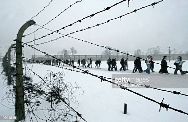 Visitors walk along the fence of former concentration camp Sachsenhausen 27 January 2004 in the eastern town of Oranienburg on the 59th Holocaust...