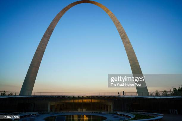 Visitors walk along the Gateway Arch near the Mississippi River in downtown St Louis Missouri on June 1 2018 The Arch features a new museum and...