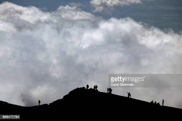 Visitors walk along the rim of a crater on the Mt Etna volcano Europe's largest and most active on September 22 2017 in Sicily Italy Wine has been...