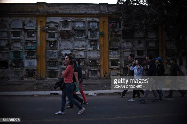 Visitors walk amid tombs and mausoleums at Guatemala's general cemetery on October 29 2016 The night tours of the cemetery to promote culture and...