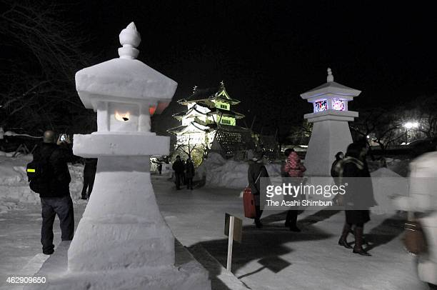 Visitors walk among candlelit snow lanterns during the Hirosaki Castle Snow Lantern Festival at Hirosaki Park on February 7 2015 in Hirosaki Aomori...