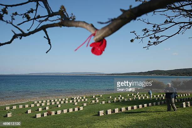 Visitors walk among headstones of mostly Australian soldiers killed during the Gallipoli Campaign at Ari Burnu Cemetery at Anzac Cove as a...