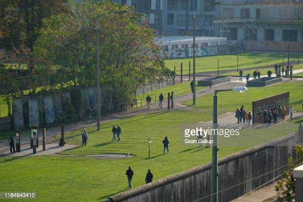 Visitors walk among memorials and preserved portions of the Berlin Wall at Bernauer Strasse on October 31 2019 in Berlin Germany November 9 will mark...