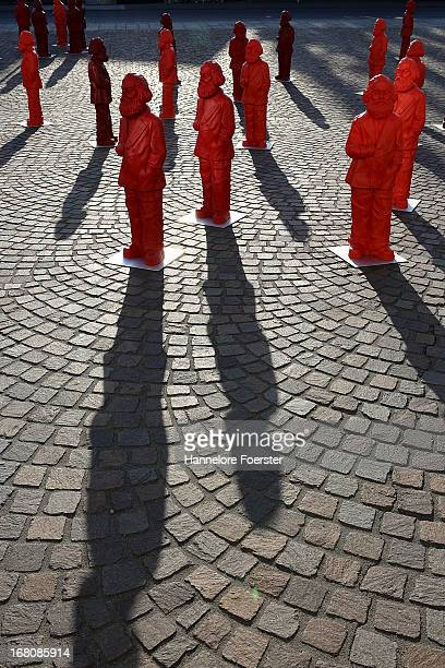 Visitors walk among some of the 500 one meter tall statues of German political thinker Karl Marx on display on May 5 2013 in Trier Germany The...