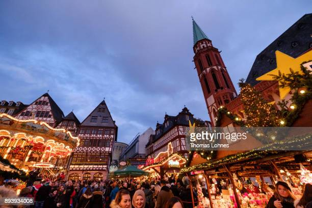 Visitors walk among stalls selling mulled wine pastries sausages Christmas decorations handicrafts and other Christmas delights at the annual...