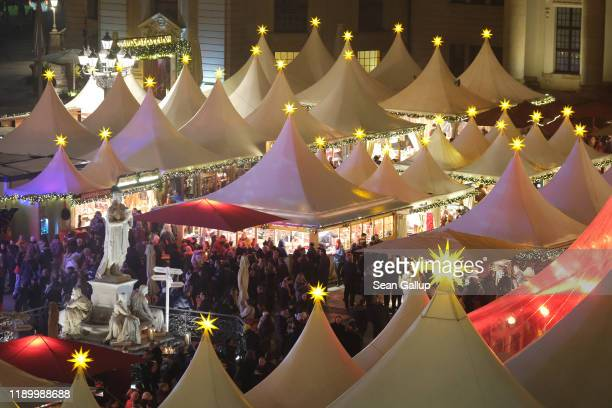 Visitors walk among tented stalls at the annual Christmas market at Gendarmenmarkt square on the market's opening day on November 25, 2019 in Berlin,...