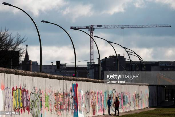 Visitors walk among the Berlin Wall at the East Side Gallery on February 5 2018 in Berlin Germany Today has been 10316 days since the Berlin Wall...