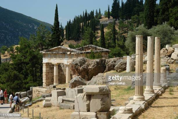 Visitors walk among the ruins of ancient Delphi on July 20 2019 at Delphi Greece Delphi is located on Mount Parnassus was an important religious site...