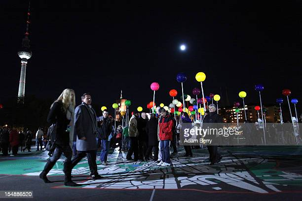 Visitors walk amongst large illuminated pins stuck into a painted 1775 scale map of Berlin in front of the Fernsehturm during celebrations marking...
