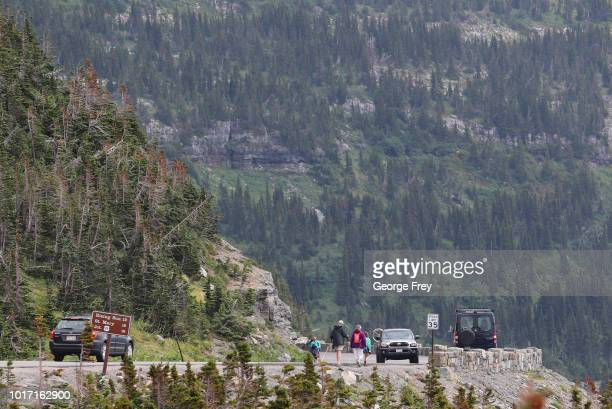 Visitors walk and cars drive along the Going To the Sun Road in Glacier National Park on July 26 2018 in West Glacier Montana Over crowding in...