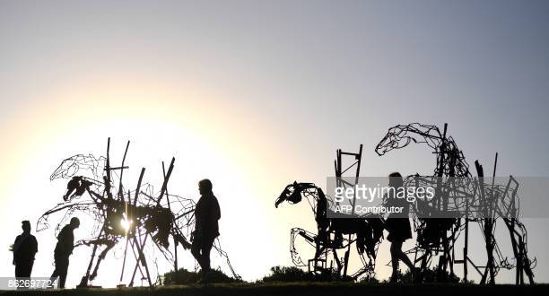 Visitors walk around a sculpture by artist Harrie Fasher as part of the 'Sculpture by the Sea' exhibition near Bondi beach in Sydney on October 18...