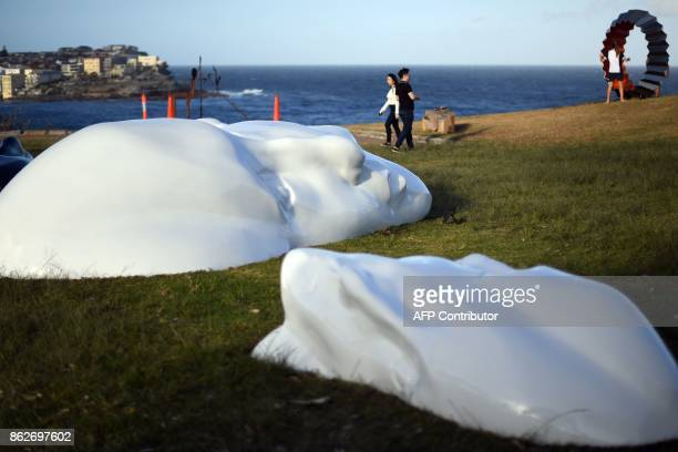 Visitors walk around sculptures by artist Sonia Payes near Bondi beach as part of the 'Sculpture by the Sea' exhibition in Sydney on October 18 2017...