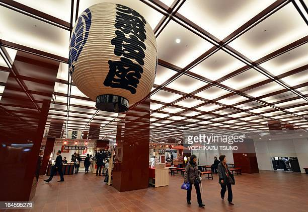 Visitors walk around the shops in an atrium of the recently rebuilt kabuki art theatre in Tokyo on March 25 2013 The theatre in the upscale Ginza...