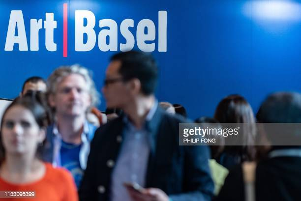 Visitors walk as the billboard of Art Basel is shown in Hong Kong on March 27, 2019.