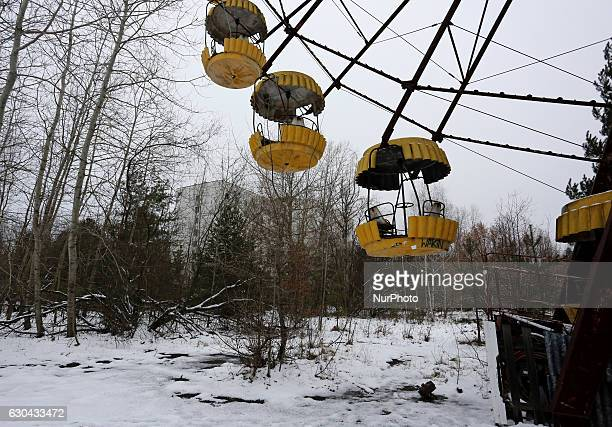 Visitors walk at the amusement park of the deserted city of Pripyat, near the Chernobyl nuclear power plant in Chernobyl, Ukraine, 22 December 2016....