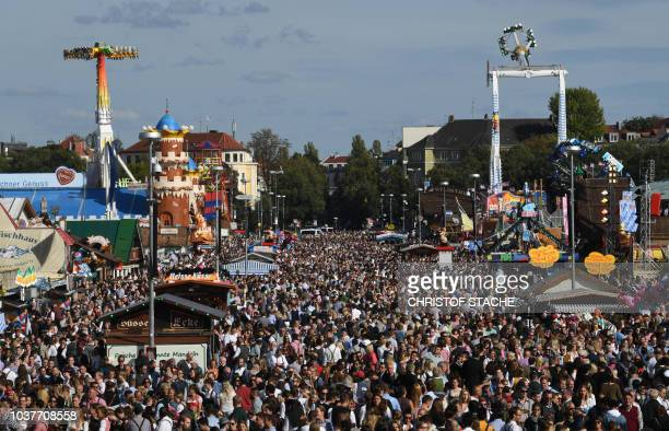 Visitors walk at the Theresienwiese fair ground of the Oktoberfest beer festival in Munich, southern Germany, on September 22, 2018. - The world's...
