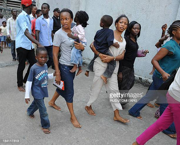 Visitors walk barefooted to watch Eyo masquerades perform during the Eyo festival in Lagos on November 26 2011 It is against the tradition to wear...