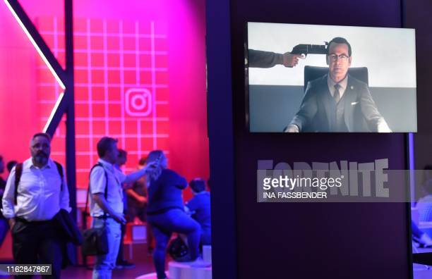 Visitors walk behind a video screen of the Fortnite computer game at the media day of the Gamescom video games trade fair in Cologne western Germany...