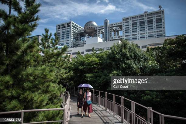 Visitors walk beneath the Hachitama spherical observation room in the Fuji Television building overlooking Odaiba Marine Park on September 18 2018 in...