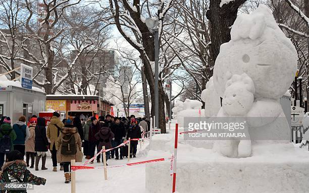 """Visitors walk beside a snow statue of """"Hello Kitty"""" during the 65th annual Sapporo Snow Festival on February 5, 2014. The week-long festival started..."""