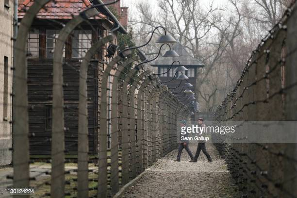 Visitors walk between barbed wire fences at the Auschwitz I memorial concentration camp site on February 15 2019 in Oswiecim Poland Next year will...