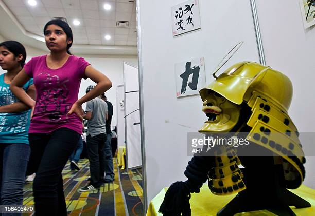 Visitors walk by a replica of a Samurai mask worn in the XII century during the 'Japan and its Ancestral Warriors' exhibition in Monterrey Mexico on...