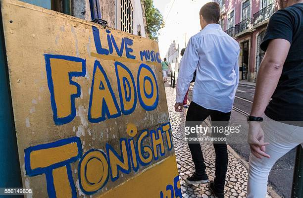Visitors walk by a sign advertising Fado performance near Lisbon Cathedral in the Parish of Santa Maria Maior one of the city's historic...