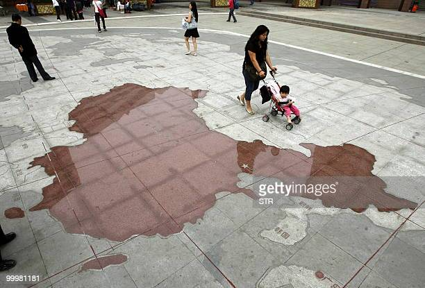 Visitors walk by a world map carved in stone with China highlighted in red at a plaza in southwest China's Chongqing municipality on May 19 2010 A...