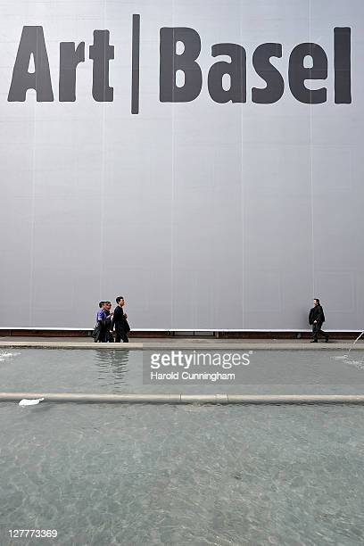 Visitors walk by an Art Basel sign on June 14 2011 in Basel Switzerland 300 art galleries selected by the fair will display works by more than 2500...