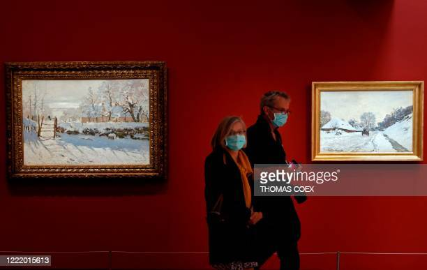 """Visitors walk by Claude Monet's painting """"La pie"""" as they visit the Orsay museum on its reopening day, on June 23 in Paris, as France eases lockdown..."""