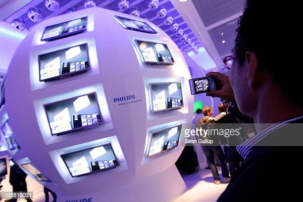 Visitors walk by LED televisions at the Philips stand at the 2010 IFA technology and consumer electronics trade fair at Messe Berlin on September 3...