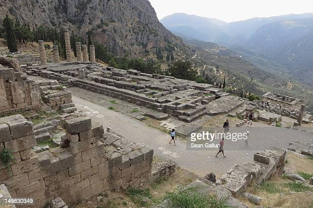 Visitors walk by the former Palace of Apollo where the oracle once prophesized the future at the ancient archeological site of Delphi on August 2...