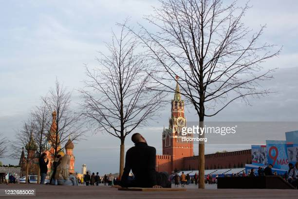 Visitors walk by the Spasskaya tower of the Kremlin and Saint Basil's Cathedral on Red Square in Moscow, Russia, on Sunday, May 2, 2021. Facing a...