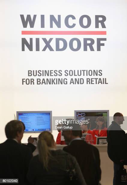 Visitors walk by the stand of German computer equipment manufacturer Wincor Nixdorf at the CeBIT technology fair the first day the fair opened to the...