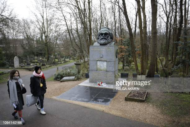 Visitors walk by the tomb of German revolutionary philosopher Karl Marx a Grade Ilisted monument in Highgate Cemetery in north London on February 5...